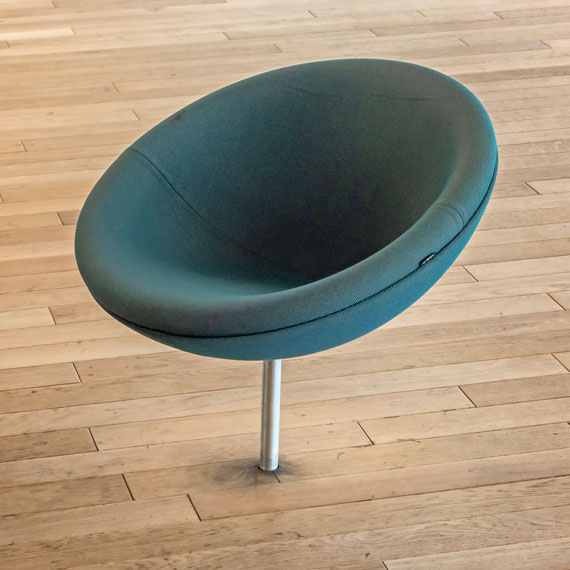 a round, green chair is mounted to the floor of a library