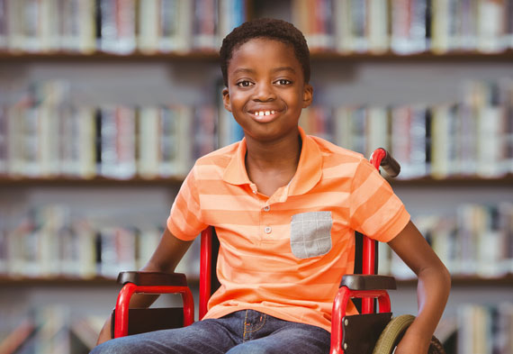 smiling African-American lad sitting in a library wheelchair